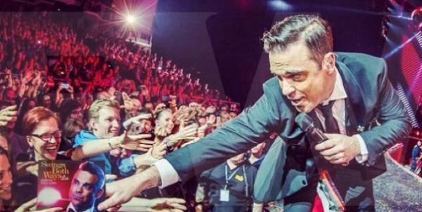 Video: Robbie Williams le quiebra el brazo a una fan en pleno recital